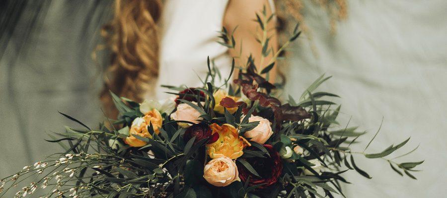 Woman with flower bouquet in bridal gown byKwiaciarnia Zielona Weranda